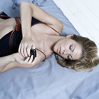 beautiful young caucasian woman lying on a bed calling by phone