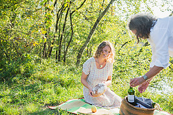 Couple preparing for a picnic by lakeshore, Bavaria Germany