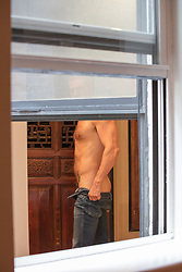 man taking off his jeans by an open window in New York City