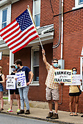 """Watsontown, PA (June 28, 2020) -- A man at a Black Lives Matter protest in rural Pennsylvania holds a """"farmers for black lives"""" sign and waves an American flag. About 200 Black Lives Matter protesters were confronted by nearly 50 counter-protesters. Local activist group """"If Not Us, Then Who?"""" organized the event."""