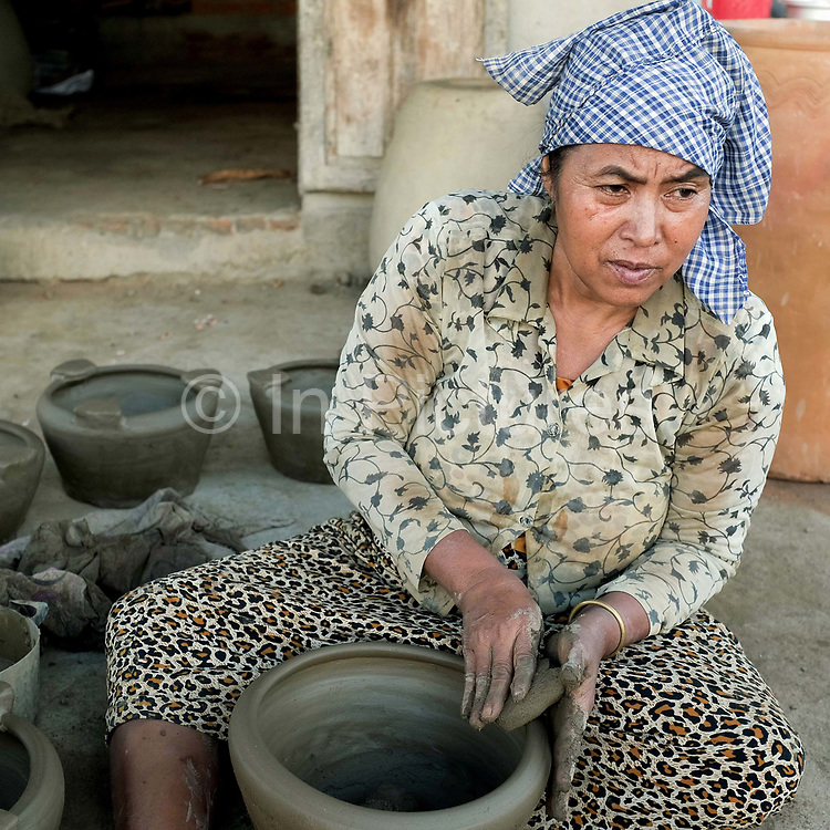 A Hindu Cham woman makes a ceramic barbeque using a traditional method in the famous pottery village of Bau Truc in Central Vietnam. Cham potters do not use a wheel to make pots, instead clay is pressed into shape using the hands. Layers of clay are added to the original piece and the potter moves around the object, pressing the clay into the desired shape. They are then put directly in the sun and completely bone dried, making them ready to be fired. Firing is done in an open pit with temperatures going up to 800 degree Celcius. The pots are arranged together and covered with layers of rice straw, which is set on fire.