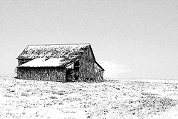 23 February 2008:  A dilapidated old red barn stands all alone on the prairie surrounded by the snow of winter and a bright blue sky<br />