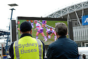 Spectators watch the 2008 Rugby League Grand Final on a big screen set up outside Olympic Stadium. Sydney, Australia