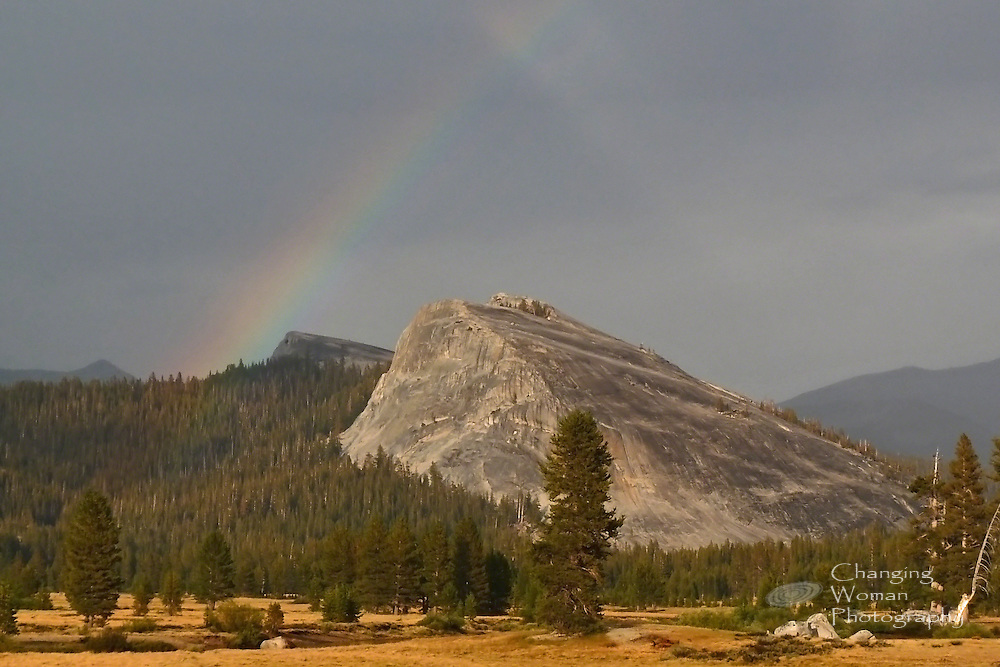 A soft-focus image shows a rainbow arcing over Yosemite's Lembert Dome during a late-summer rain.