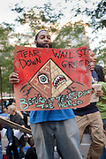 "A man holds a colorful sign reading ""Tear down Wall St greed before it tears down the world."""