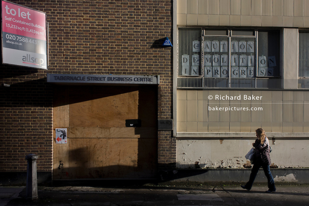 A passer-by walks beneath a derelict and soon-to-be demolished building in the London borough of Islington, near the City of London. The Tabernacle Business Centre has been earmarked for redevelopment by Allsop, the property consultancy, tasked with the demolition of this property. The entrance has already been ply-boarded up and closed for business.