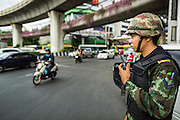 29 MAY 2014 - BANGKOK, THAILAND:  A Thai soldier watches traffic in Victory Monument during a military operation to shut the Monument down. After a series of protests around Victory Monument earlier in the week, the Thai army Thursday shut down vehicle access to the area, one of the main intersections in Bangkok, and kept people out of the area. Thousands of soldiers surrounded the Monument and effectively locked the area down. There were no protests at Victory Monument for the first time in the week since the coup deposed the elected civilian government.  PHOTO BY JACK KURTZ