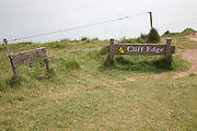 Wooden signs warning of the danger of cliff erosion at the top of the sheer cliffs at Beachy Head, East Sussex, England