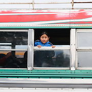 A young girl leans out a window on a chicken bus behind the Mercado Municipal (town market) in Antigua, Guatemala. From this extensive central bus interchange the routes radiate out across Guatemala. Often brightly painted, the chicken buses are retrofitted American school buses and provide a cheap mode of transport throughout the country.