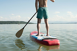 Rear view of a mature man paddleboarding in the lake, Bavaria, Germany