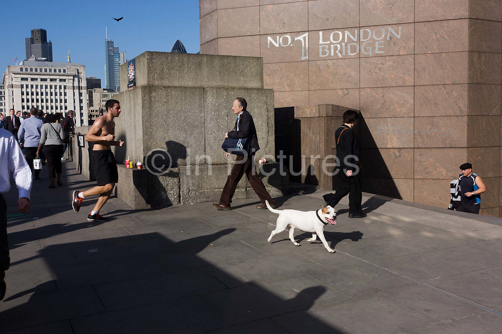 A jogger runs through passing commuters, on the southern end of London Bridge. With his pet dog, the man jogs past down towards the river down nearby steps. The City of London is a geographically small City within Greater London, England, the historic core of London from which, along with Westminster, the modern conurbation grew. The City's boundaries have remained constant since the Middle Ages but it is now only a tiny part of Greater London. This is a major financial centre, often referred to as just the City or as the Square Mile, as it is approximately one square mile (2.6 km) in area. London Bridge's history stretches back to the first crossing over Roman Londinium, close to this site and subsequent wooden and stone bridges have helped modern London become a financial success.