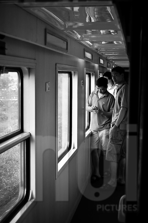 Vietnamese men stand in the corridor of a train heading to Hue, Vietnam, Asia