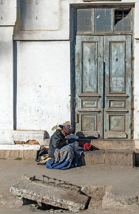 Poor, woman with child on a street in Antananarivo, Madagascar.