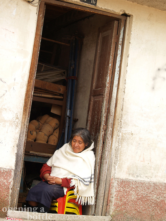 An Otavaleño woman sits at the Saturday market in the town of Otavalo, Ecuador.