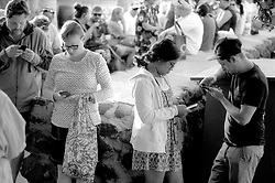 An unidentified quartet of people waiting to board a boat at the in Lahaina, Hawaii busy themselves with their smartphones, Friday, March 4, 2016. (Photo by D. Ross Cameron)