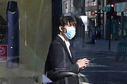 Man wearing a face mask waits at a bus stop on Oxford Street, Londons main shopping and retail area normally full of thousands of shoppers and traffic is virtually deserted due to the Coronavirus outbreak on 23rd March 2020 in London, England, United Kingdom. Following government advice most shoppers are staying at home leaving the streets quiet, empty and eerie. Coronavirus or Covid-19 is a new respiratory illness that has not previously been seen in humans. While much or Europe has been placed into lockdown, the UK government has announced more stringent rules as part of their long term strategy, and in particular social distancing.