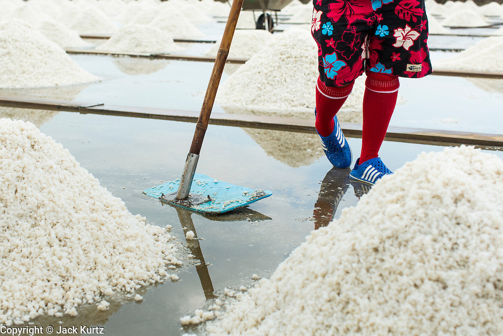 24 APRIL 2013 - SAMUT SONGKHRAM, SAMUT SONGKHRAM, THAILAND: A worker in the salt fields near Samut Songkhram, Thailand. The 2013 salt harvest in Thailand and Cambodia has been impacted by unseasonably heavy rains. Normally, the salt fields are prepped for in December, January and February, when they're leveled and flooded with sea water. Salt is harvested from the fields from late February through May, as the water evaporates leaving salt behind. This year rains in December and January limited access to the fields and rain again in March and April has reduced the amount of salt available in the fields. Thai salt farmers are finishing the harvest as best they can, but the harvest in neighboring Cambodia ended 6 weeks early because of rain. Salt has traditionally been harvested in tidal basins along the coast southwest of Bangkok but industrial development in the area has reduced the amount of land available for commercial salt production and now salt is mainly harvested in a small part of Samut Songkhram province.      PHOTO BY JACK KURTZ