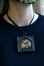 Bonhams picture specialist May Matthews wears 'Morning', an enamelled metal plaque, inscribed and dated 'Morning/1914' by Phoebe Anna Traquair HRSA (1862-1936).  The plaque is mirrored in the mask May is wearing.