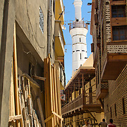 A mosque's minaret rises from a Rashid back lane.