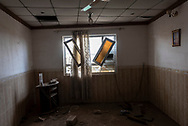 View through a broken home window in Qaraqosh, Iraq, a mostly Christian city near Mosul that was occupied by ISIS from 2014 to 2016. ISIS caused considerable destruction to homes, businesses, and churches. On the right a picture of the Virgin Mary still hangs on the wall. (May 5, 2017)