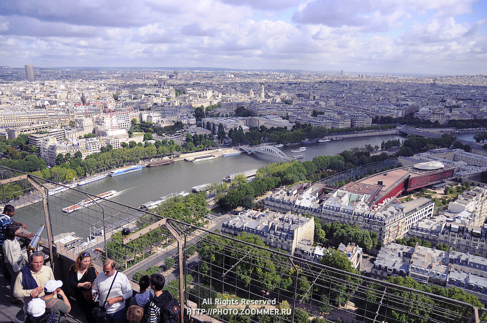 Tourists on Eiffel Tower 2nd level looking down to Paris Seine river and buildings
