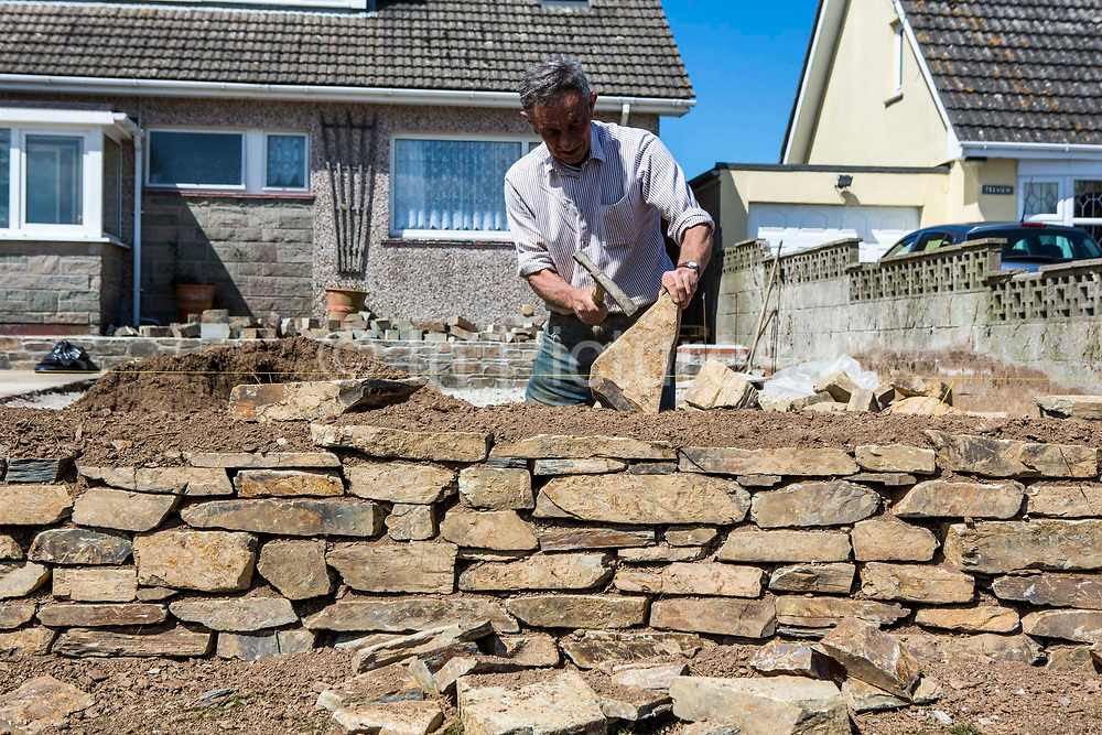 A British stonemason hammers a sandstone while constructing a wall in the front garden of a residential home in Wadebridge, Cornwall, UK.