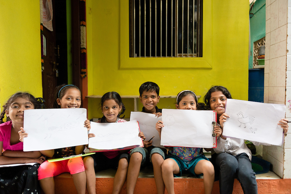 School children show their work in a slum in the Cuffe Parade neighborhood of Mumbai