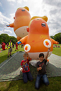 Children sitting with their official crowdfunder balloons in front of  the six metre high inflatable TrumpBaby balloon and the three metre high mini Trump Baby at the demo on the Meadows in Edinburgh, Scotland. United Kingdom. 14th July 2018.