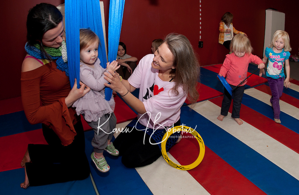 """Nicole Heal assists her daughter Athena as she tries the """"silk swing"""" with direction from  Artsfest's Erin Lovett Sherman during """"Circus and Performing Arts for Kids"""" Monday afternoon at the Laconia Community Center.   (Karen Bobotas/for the Laconia Daily Sun)"""
