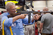 """16 MAY 2009 -- PHOENIX, AZ: A man looks at a replica of a Thompson submachine gun (""""Tommy Gun"""") at the Thompson booth at the NRA convention in Phoenix Saturday. About 60,000 people were expected to attend the trade show at the 138th annual National Rifle Association Annual Meeting in the Phoenix Convention Center in Phoenix, AZ. Photo by Jack Kurtz"""