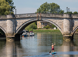 © Licensed to London News Pictures. 21/05/2020. London, UK. A man paddle boards along the River Thames in Richmond in South West London as weather experts predict the another warm day with a high of 27c. Last week the Government eased the law on lockdown to let people spend more time outside to enjoy sunbathing and picnicking. Photo credit: Alex Lentati/LNP