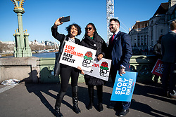 © Licensed to London News Pictures. 05/03/2019. London, UK.  From left to right MPs Chi Onwhtah (for Newcastle upon Tyne Central), Kate Osamor (for Edmonton), Paul Sweeney (for Glasgow North) film themselves themselves following a stunt on Westminster bridge.  MPs dropped a banner reading Love Socialism Hate Brexit over Westminster Bridge and light red flares in a stunt which prompted police to clear the demonstrating members of parliament. MPs pictured on the bridge are:<br /> <br /> Clive Lewis,  <br /> Lloyd Russell Moyle,  <br /> Kate Osamor,  <br /> Marsha de Cordova, <br /> Sandy Martin, <br /> Alex Sobel,  <br /> Preet Gill,  <br /> Rachael Maskell,  <br /> Luke Pollard,  <br /> Chi Onwurah, <br /> Paul Sweeney,  <br /> Ged Killen, <br /> Rupa Huq,  <br /> <br /> Photo credit: Guilhem Baker/LNP