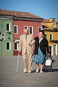 Elderly couple walking down Burano's Piazza Baldassarre Galuppi.Island of Burano, Venice, Italy, Europe