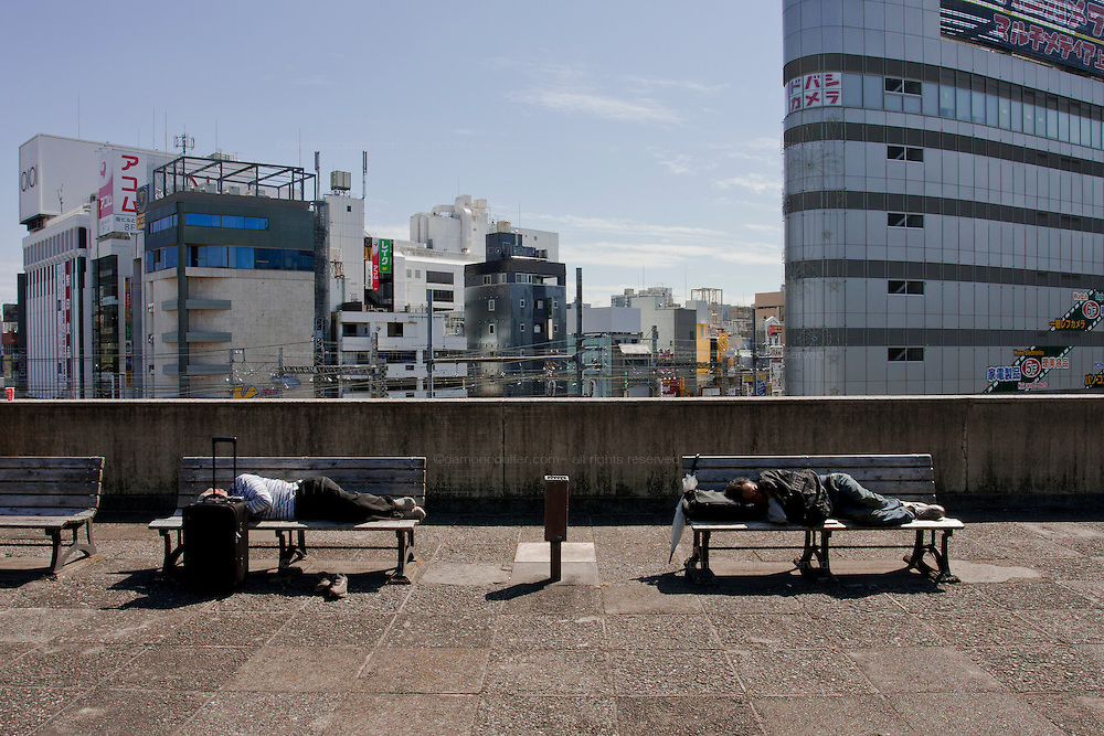 Homeless people sleeping on Park benches in Ueno Park, Tokyo, Japan. Friday, September 25th 2009