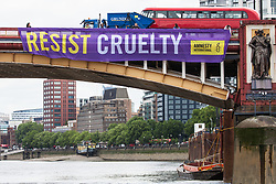 London, UK. 3 June, 2019. One of five brightly-coloured banners bearing the slogans 'Resist Trump', 'Resist sexism', 'Resist racism', 'Resist hate' and 'Resist cruelty' is dropped on Vauxhall Bridge in view of the US embassy by activists from Amnesty International at the beginning of President Donald Trump's three-day state visit to the UK. Amnesty International has written to Prime Minister Theresa May has written to Theresa May to urge her to raise human rights issues directly with the US President.