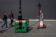 A man with striped jacket with a lamp post shadow against a grey construction hoarding in central London's Trafalgar Square. Painting work is being carried out to the street lighting lamp post, a green plastic fence surrounding the wet paint while the post's upright has created a strong linear theme to the pavement and background hoarding that screens other work.