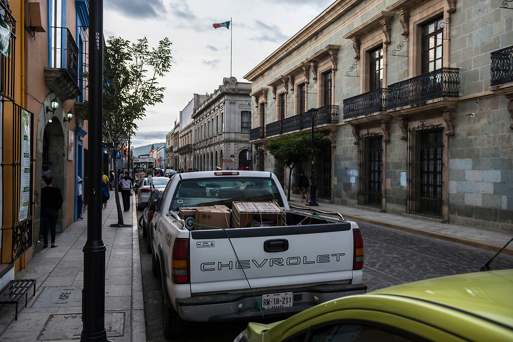 Cars are parallel parked on a street in Oaxaca, Mexico. Pedestrians are on the sidewalks.