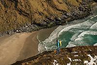 Hiker on ridge overlooking Kvalvika beach, Moskenesøy, Lofoten Islands, Norway