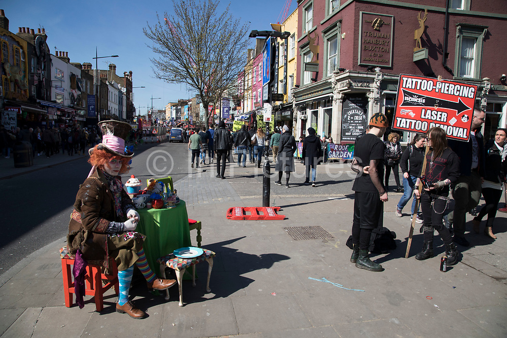 Street performer dressed up as the Mad Hatter, from the Alice in Wonderland story sits at his table having his own Mad Hatters tea party in Camden Town, London, England, United Kingdom. Camden Town is famed for its market, warren of fashion and shops near Regent's Canal, and is a haven of alternative counter culture.