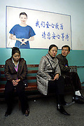 The mother of Fan Yuting (L), waits for news while her daughter is on surgery. The waiting room of the hospital has a sign which advises that the hospital staff is doing their best work and relatives should wait quietly for news.
