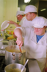 Group of adults with Downs Syndrome working in kitchen,
