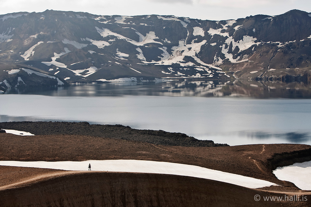 The lake Askja and tourists standing on top of geothermal crater - Ferðamaður á bakka Vítis og Öskjuvatn í fjarska