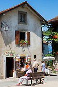 Tourists shopping for souvenirs in the old medieval district of Yvoire by Lac Leman, Lake Geneva, France