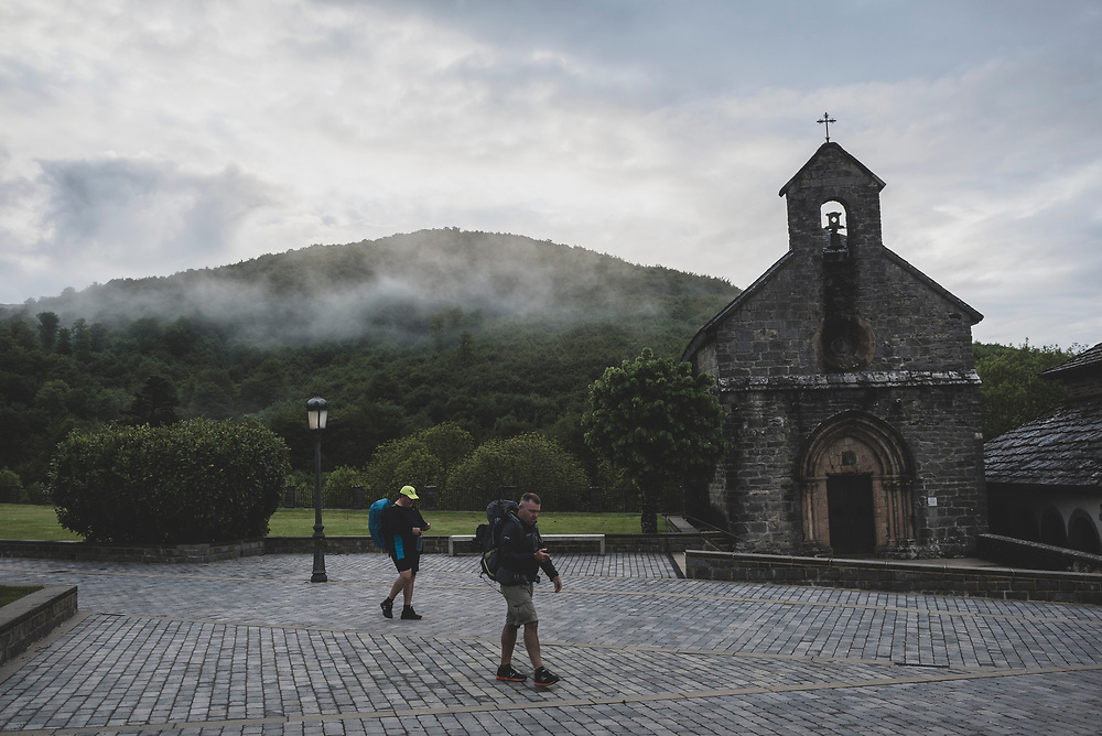 At 7:00 a.m., two pilgrims start the day's walk on the Camino de Santiago, passing the 13th-century Iglesia de Santiago o de los Peregrinos in the village of Roncesvalles, Spain (May 29, 2018)<br /> <br /> DAY 2: RONCESVALLES TO ZUBIRI -- 22 KM