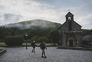 At 7:00 a.m., two pilgrims start the day's walk on the Camino de Santiago, passing the 13th-century Iglesia de Santiago o de los Peregrinos in the village of Roncesvalles, Spain (May 29, 2018)<br />