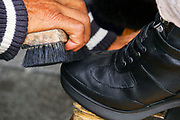 Client is having his shoe polished at a Shoeshine stand. Close-up of the hand, brush and boot, Photographed in Plovdiv, Bulgaria