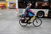 Een vrouw fietst door het centrum van Nijmegen terwijl ze wordt ingehaald door een stadsbus.<br /> <br /> A woman cycles in the city center of Nijmegen while being passed by a bus.