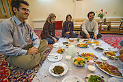 Atefeh Fotowat, a high school student and aspiring fashion designer (second from left in blue jeans), enjoys dinner with her family in their elegant four-story home in Isfahan, Iran.  (Atefeh Fotowat is featured in the book What I Eat: Around the World in 80 Diets.)