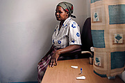 A woman waits for the results of her HIV test at a clinic in Mabote, Mozambique. HIV testing determines whether or not you are infected with the Human Immunodeficiency Virus (HIV). This virus destroys the body's ability to fight off illness, and is the cause of AIDS (Acquired Immune Deficiency Syndrome).