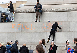 © Licensed to London News Pictures. 07/10/2019. London, UK. An Extinction Rebellion activists writes 'Rebel now' on Nelson's Column plinth in Trafalgar Square, central London with a scaffolding tower. Activists are converging on Westminster blockading roads in the area for at least two weeks calling on government departments to 'Tell the Truth' about what they are doing to tackle the Emergency. Photo credit: Peter Macdiarmid/LNP